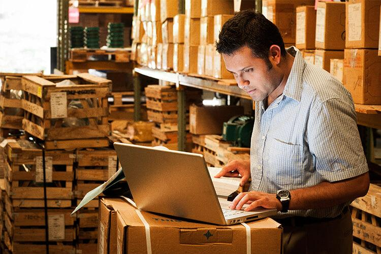 person in warehouse on laptop
