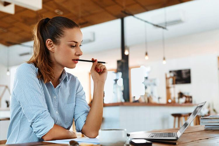 Woman with pen in mouth looking at laptop
