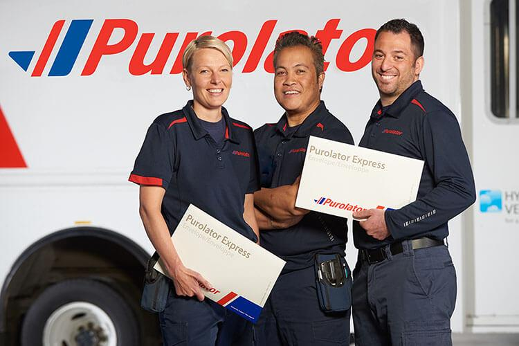 Three Purolator employees in front of truck
