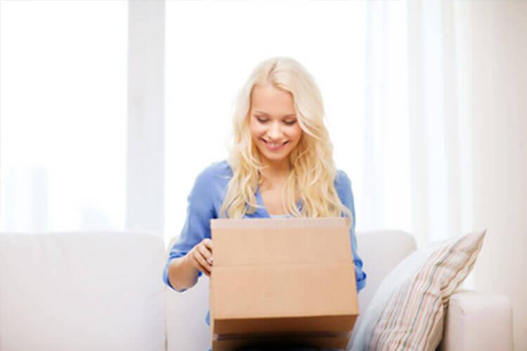 Woman sitting on couch opening box